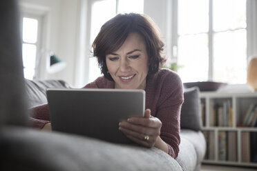 Woman at home lying on the sofa using tablet - RBF05404