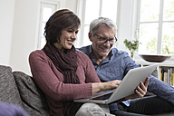 Smiling mature couple at home on the sofa using laptop - RBF05407