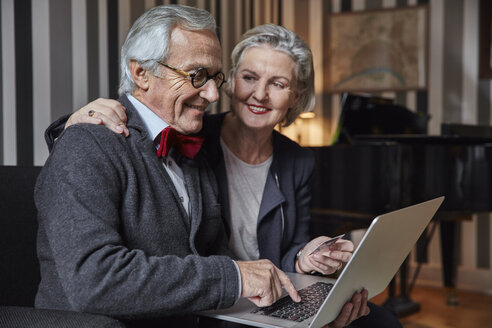 Happy senior couple shopping online at home - RHF01685
