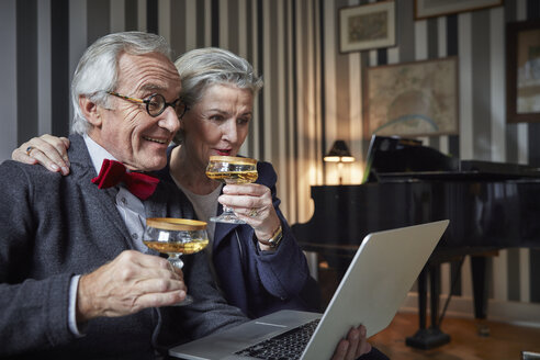 Happy senior couple drinking champagne and using laptop at home - RHF01688