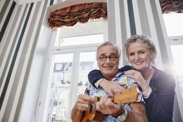 Happy senior couple with man in Hawaiian shirt playing ukulele - RHF01691