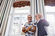 Happy senior couple with man in Hawaiian shirt playing ukulele - RHF01694