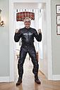 Happy senior man in motorcycle suit at home - RHF01697
