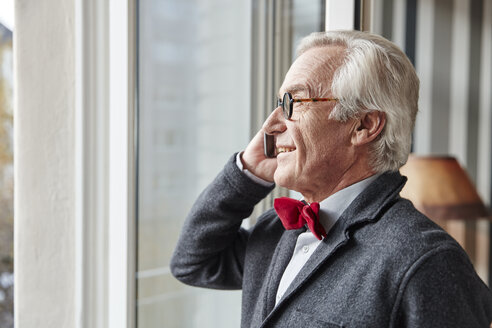 Smiling senior man on the phone at the window - RHF01703