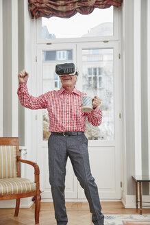 Senior man holding beer mug wearing VR glasses - RHF01706