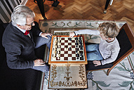 Grandfather and grandson playing chess in living room - RHF01718