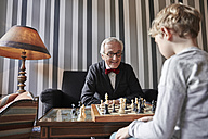 Grandfather and grandson playing chess in living room - RHF01724