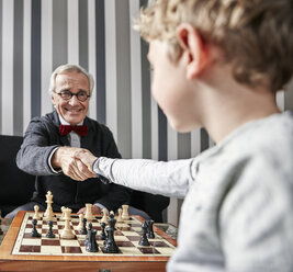 Grandfather and grandson shaking hands over chessboard - RHF01727