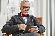 Senior man sitting on chair holding tablet - RHF01730