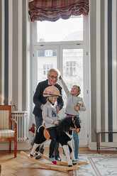 Grandfather and grandchildren playing with rocking horse - RHF01745