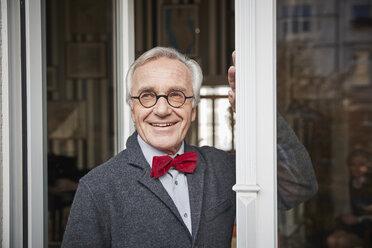 Smiling senior man looking out of window - RHF01748