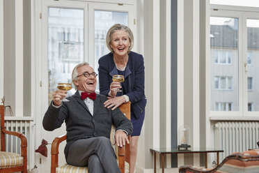 Happy senior couple drinking champagne at home - RHF01754