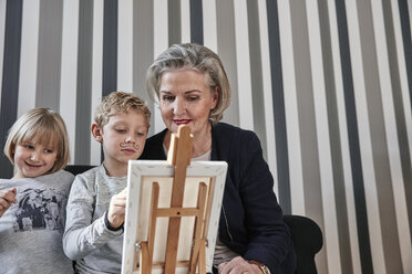 Grandmother and grandson with Dali moustache at easel with girl watching - RHF01760