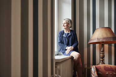 Senior woman looking out of window - RHF01763