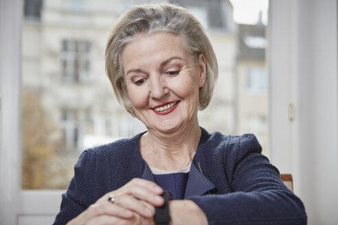 Smiling senior woman looking at watch - RHF01766