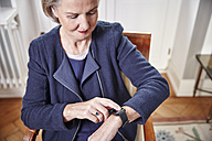 Senior woman sitting on chair looking at smartwatch - RHF01769