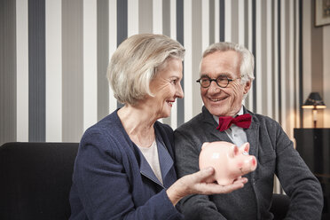 Happy senior couple sitting on couch with piggy bank - RHF01775