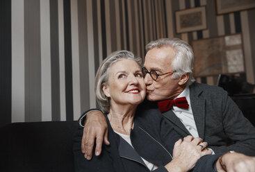 Senior man kissing wife on couch - RHF01778
