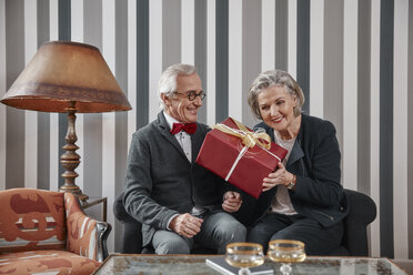 Happy senior couple sitting on couch with gift - RHF01781