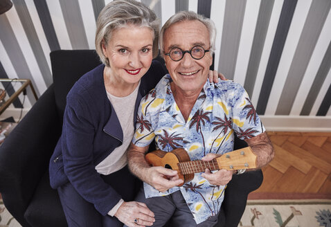 Happy senior couple with man in Hawaiian shirt playing ukulele - RHF01787