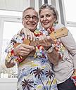 Happy senior couple with man in Hawaiian shirt playing ukulele - RHF01790