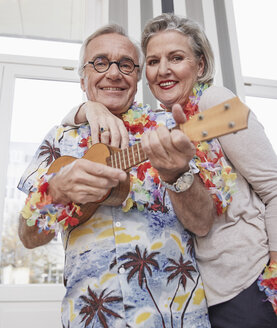Happy senior couple with man in Hawaiian shirt playing ukulele - RHF01790