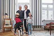 Grandparents and grandchildren with rocking horse in living room - RHF01793