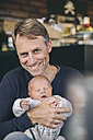 Portrait of smiling mature father holding his sleeping baby in cafe - MFF03415