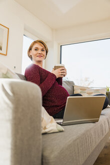 Pregnant woman with laptop on couch holding mug - UUF09586