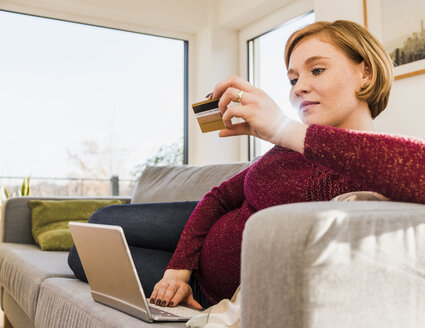Pregnant woman on couch shopping online - UUF09589