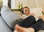 Young woman lying on couch using tablet - UUF09598