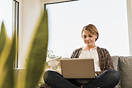 Pregnant woman sitting on couch using laptop - UUF09604