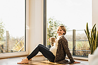 Smiling pregnant woman sitting on floor enjoying a drink in mug - UUF09607