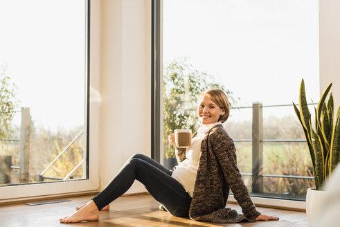 Smiling pregnant woman sitting on floor enjoying a drink in mug - UUF09607