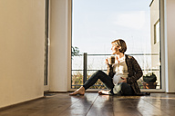 Pregnant woman sitting on floor enjoying a drink in mug - UUF09610
