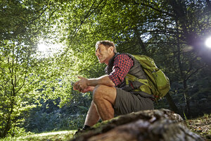 Hiker in forest sitting on tree trunk, holding smart phone - FMKF03326