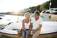 Senior couple sitting on edge of a boat on the beach at evening twilight - HAPF01259