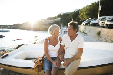 Senior couple sitting on edge of a boat on the beach at evening twilight - HAPF01259