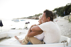 Senior couple relaxing in a boat on the beach in the evening - HAPF01265