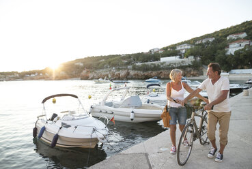 Senior couple with bicycle walking on quay at evening twilight - HAPF01268