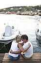Senior couple sitting head to head on jetty - HAPF01274