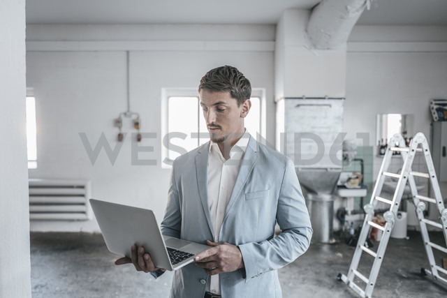 Businessman using laptop in empty loft - KNSF00824