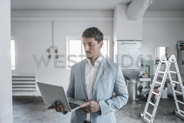 Businessman using laptop in empty loft - KNSF00824 - Kniel Synnatzschke/Westend61