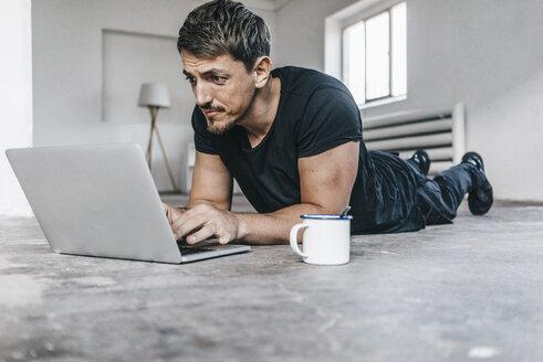 Man lying on floor using laptop in empty loft - KNSF00839