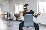 Man sitting on chair in empty loft wearing VR glasses - KNSF00842