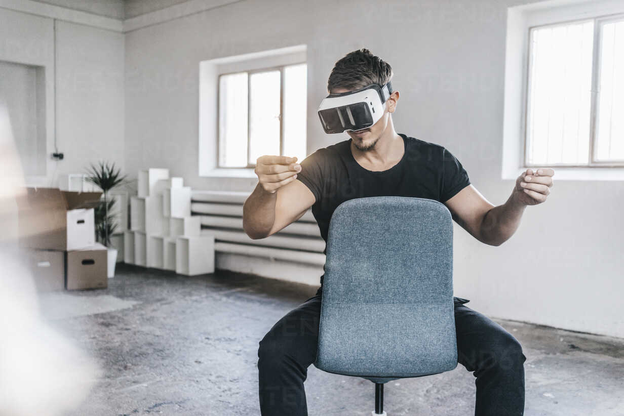 Man sitting on chair in empty loft wearing VR glasses - KNSF00842 - Kniel Synnatzschke/Westend61