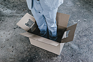 Businessman standing inside cardboard box - KNSF00851