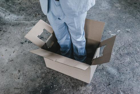 Businessman standing inside cardboard box - KNSF00851
