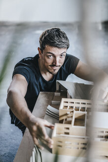 Portrait of confident architect working on architectural model - KNSF00863