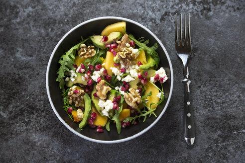 Bowl of avocado salad with rocket, pomegranate seed, kaki, feta and walnuts - SARF03102